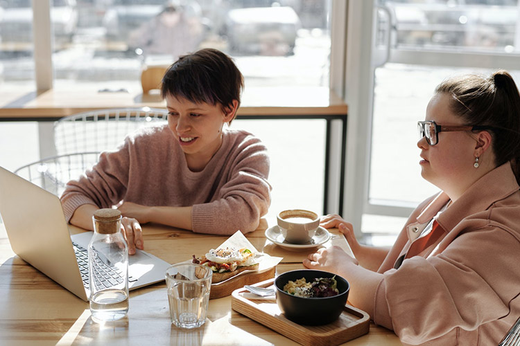 Two people at a coffee table with a laptop and coffee, one has Down Syndrome