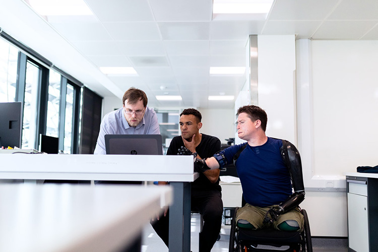 Three men around a laptop. One is a wheelchair user and amputee